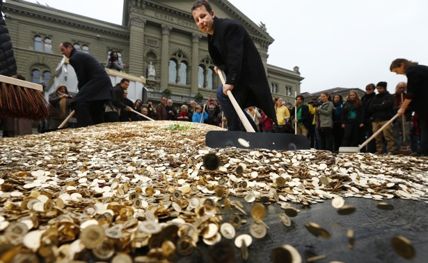 Swiss backers of a minimum income spread out coins in Bern. Denis Balibouse/Reuters