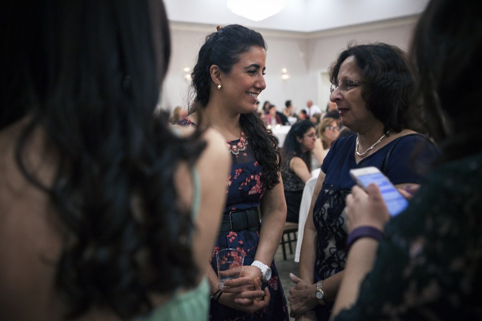 Anna Irani, 29, greets a friend at a Nowruz event hosted by the Zoroastrian Association of Metropolitan Washington at Kamran Dar-e Mehr in March of 2016. Emily Jan/Atlantic