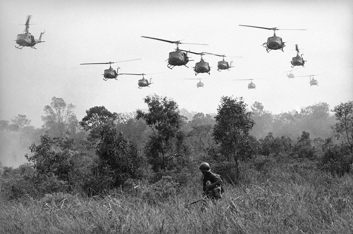 Hovering U.S. Army helicopters pour machine-gun fire into tree lines to cover the advance of Vietnamese ground troops in an attack on a Viet Cong camp 18 miles north of Tay Ninh, Vietnam, on March 29, 1965; Horst Faas