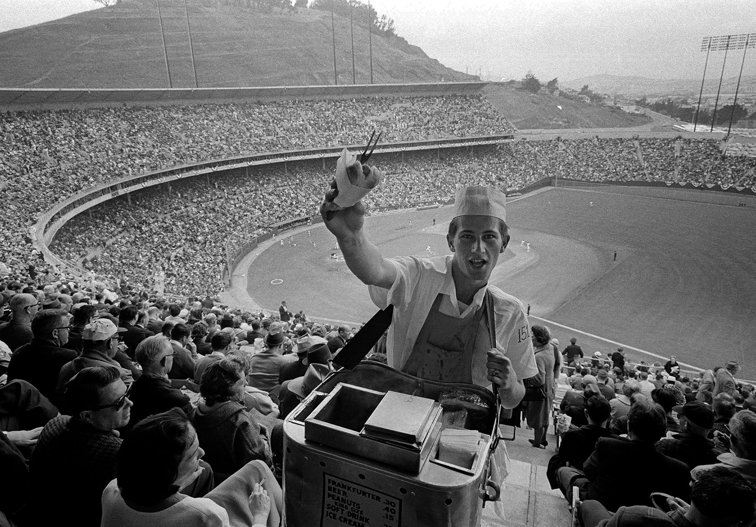 A hot dog vendor plies his wares amid a large crowd that turned out at Candlestick Park to watch the San Francisco Giants play their opening home game of the 1965 season against the Pittsburgh Pirates on April 20, 1965.