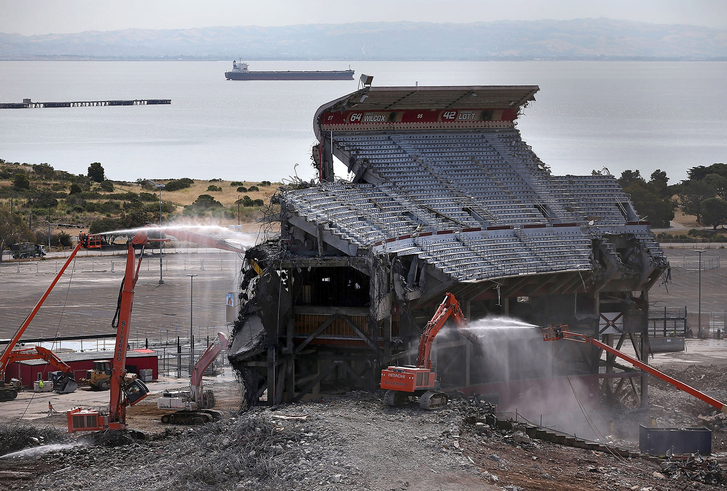 Workers spray water as a section of Candlestick Park is demolished on June 9, 2015 in San Francisco, California.