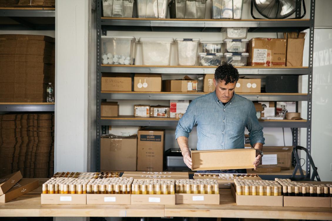 Zeke Freeman, owner and founder of Bee Raw Honey, packaging raw honey tasting kits.
