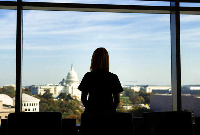 An experienced looks out of her office window at K Street
