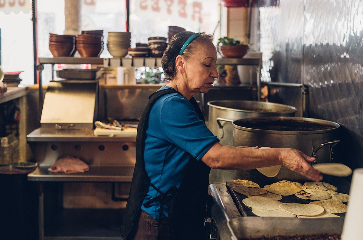 A woman cooking tortillas at Birrieria Reyes de Ocotlan