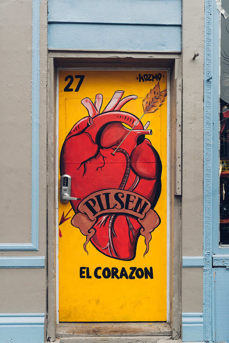 A yellow door in Pilsen with a large realistic heart painted on it and the words el corazon
