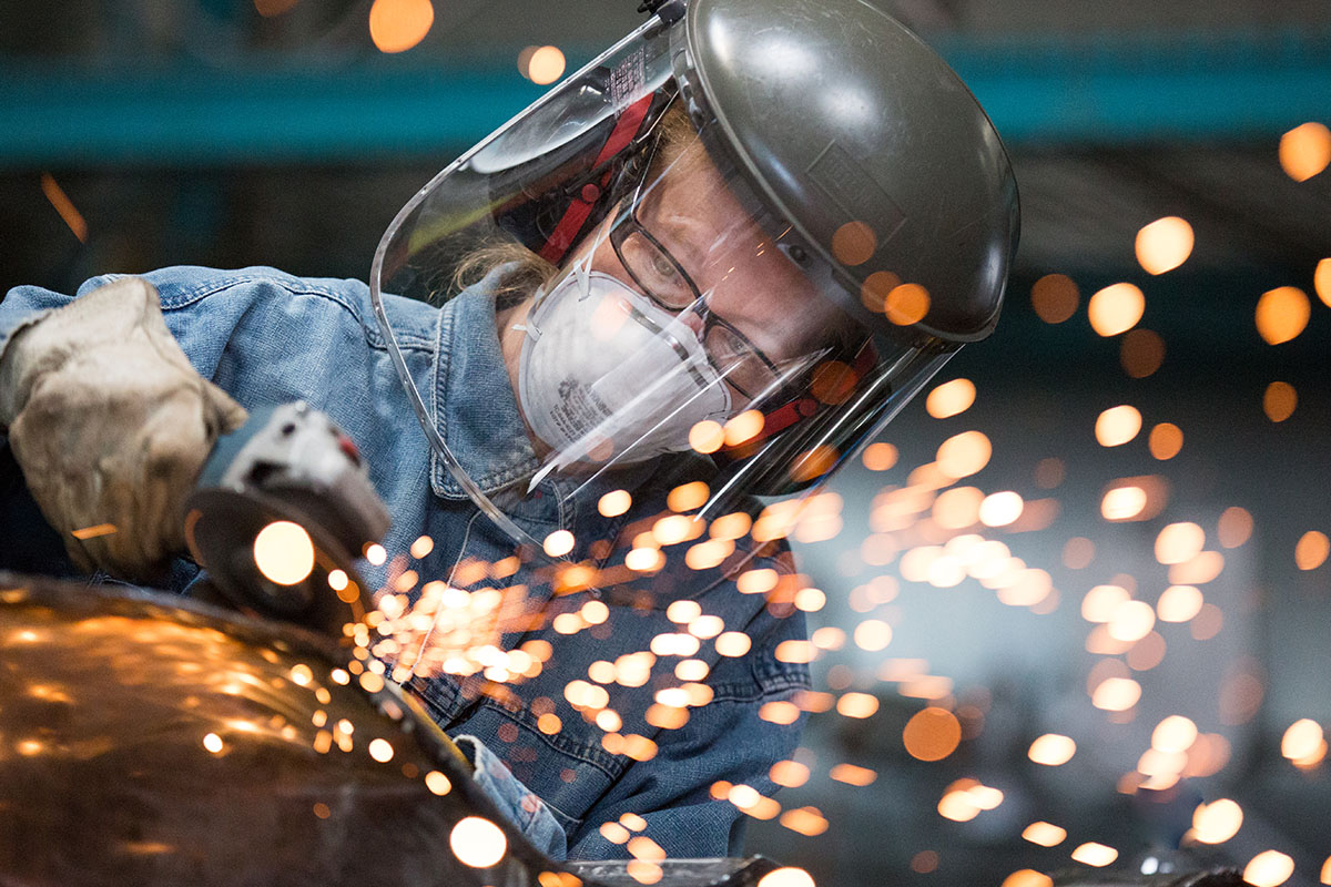 Metalworker soldering with mask on. Sparks flying.