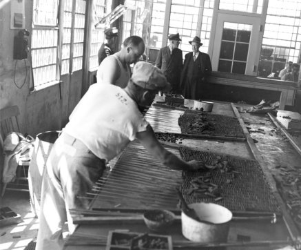 Black and white photo of two white male prison employees overseeing two white male prisoners in white uniforms working in the prison's rubber mat shop.