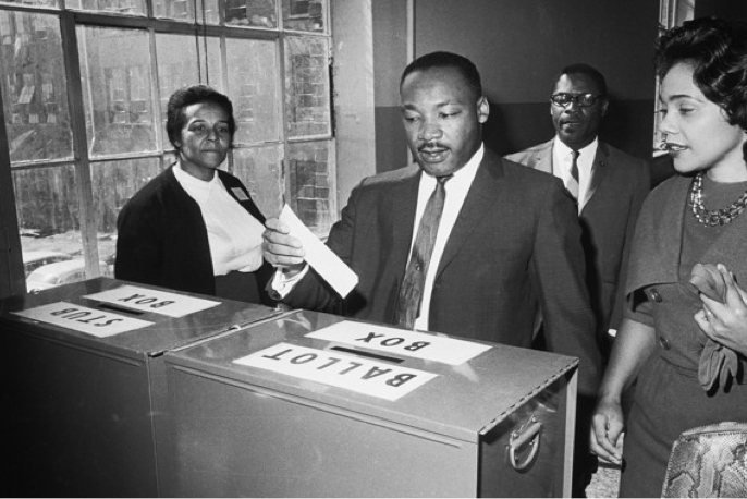 Martin Luther King Jr. and Coretta Scott King placing voting ballot