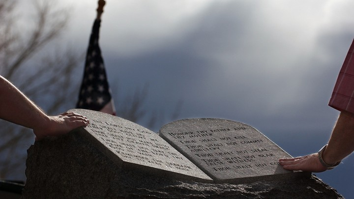 Two people touch the Ten Commandments Monument