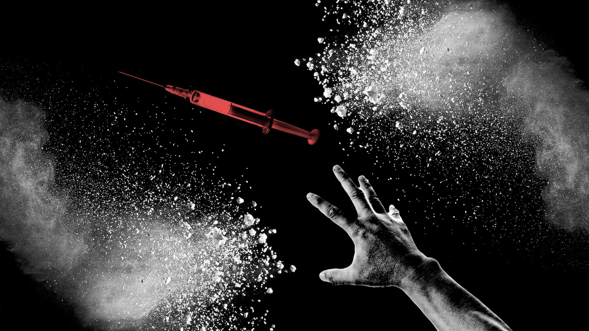 A hand reaching for a needle among white powder