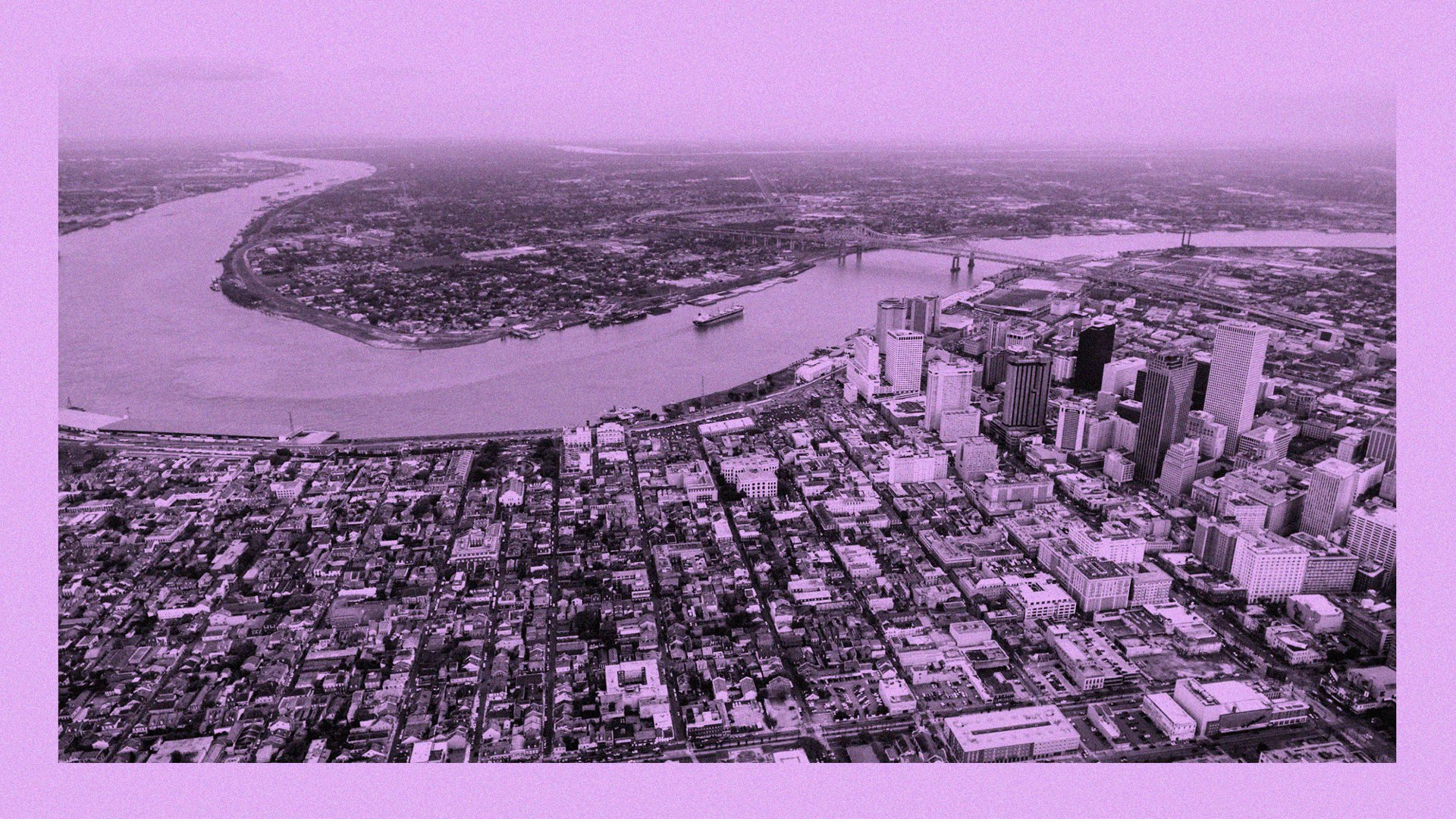A drone photo of downtown New Orleans and the Mississippi River, with the French Quarter in the foreground and the West Bank in the distance