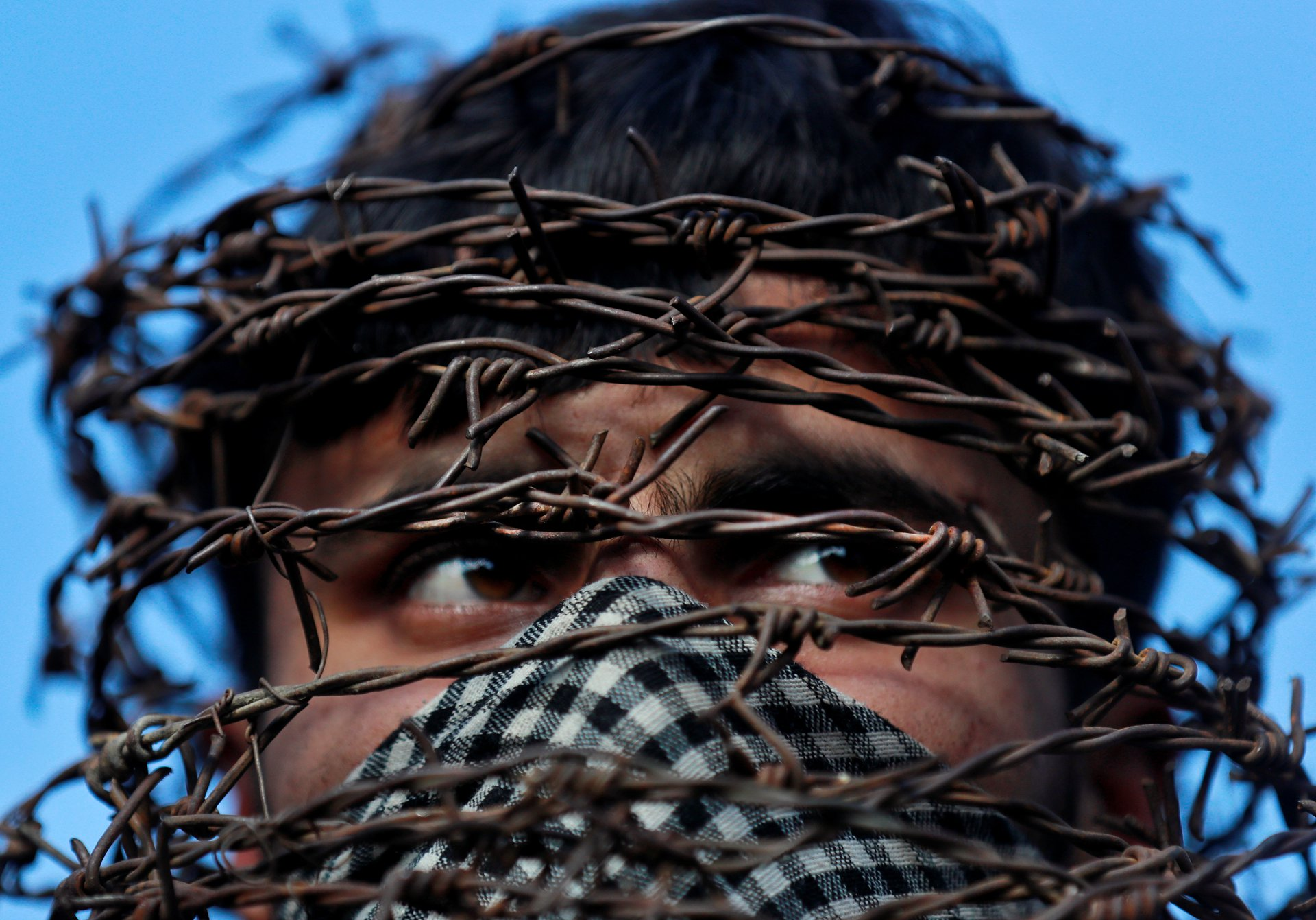 A masked Kashmiri man with his head covered with barbed wire attends a protest in Srinagar.