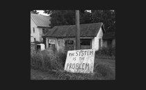 """Black and white photo of ruined house with hand-painted sign """"The System Is the Problem"""""""