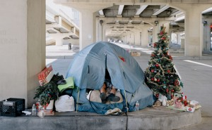 photograph of tent and Christmas tree under an overpass