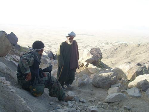 Afghan civilian walks past resting Afghan National Army soldier