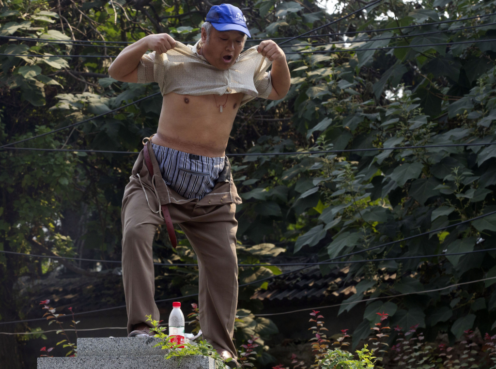 A petitioner lifts his shirt to show his injuries as he climbs a pillar to protests his own grievances near the Jinan Intermediate People's Court in Jinan in eastern China's Shandong province on Thursday Aug. 22, 2013. Ousted populist Chinese politician Bo Xilai went on trial Thursday on charges of bribery, embezzlement and abuse of power, marking the ruling Communist Party's attempts to draw a line under one of its most lurid political scandals in decades. Individual protestors have turned up at the court hoping to take advantage of media attention around Bo's trial to air their own grievances about China's legal system. (AP Photo/Ng Han Guan