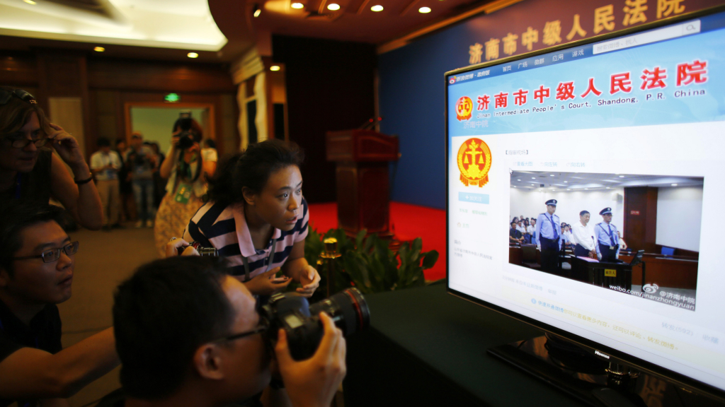 A journalist takes pictures of a screen displaying a court's microblog page showing disgraced Chinese politician Bo Xilai standing trial inside the court, in Jinan, Shandong province August 22, 2013. Bo appeared in public for the first time in more than a year on Thursday to face trial in eastern China, the final chapter of the country's most politically charged case in more than three decades. REUTERS/Carlos Barria