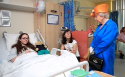 Queen Elizabeth II speaks to Amy Barlow, 12, from Rawtenstall, Lancashire, and her mother, Kathy, during a visit to the Royal Manchester Children's Hospital in Manchester, Britain, on May 25.