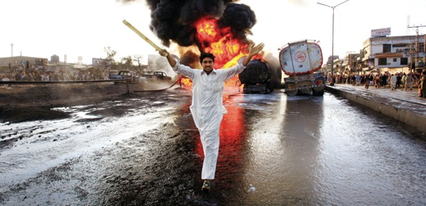 Set ablaze by roadside bombs, oil trucks bearing fuel for NATO forces burn as bystanders react in Peshawar, northwest Pakistan on February 8, 2011.