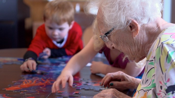 A Still From Evan Briggs S Doentary Present Perfect Shows An Elderly Resident Doing Puzzle With Preschoolers