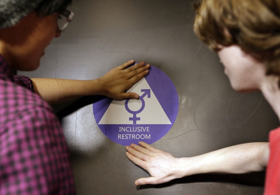 Two students place a new sticker on the door at the ceremonial opening of a gender neutral bathroom at Nathan Hale High School on May 17 in Seattle.