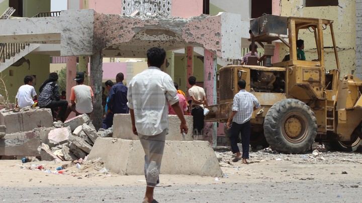 People gather near the site of a suicide car bombing Monday in Aden, Yemen