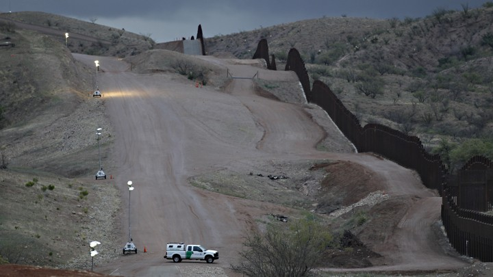 Customs and Border Patrol agent patrols along the international border after sunset in Nogales, Ariz.