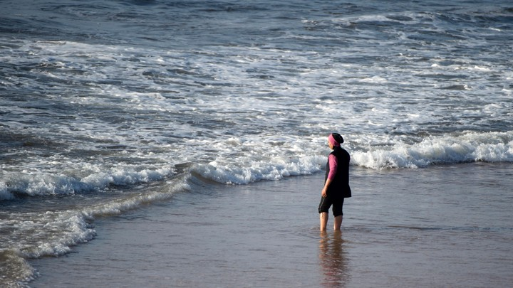 A women wearing a burqini at the beach.