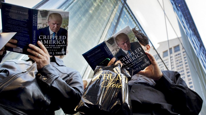 "Two people photographed from below read Donald Trump's book, ""Crippled America."""