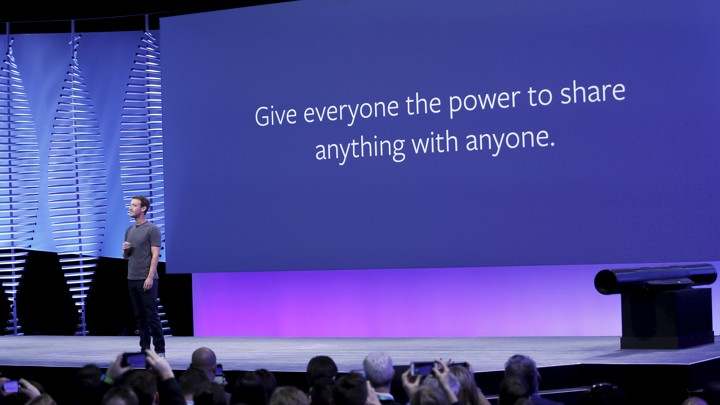"Mark Zuckerberg stands in front of a slide that says ""Give everyone the power to share anything with anyone."""