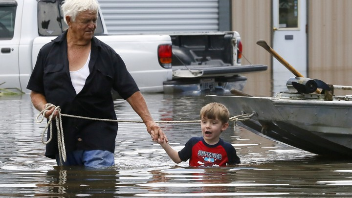 Richard Rossi and his 4 year old great grandson, Justice, wade through water in search of higher ground.