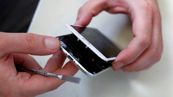 A technician repairing a broken iPhone