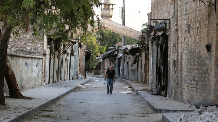 A man walks near damaged shops in the Syrian city of Aleppo