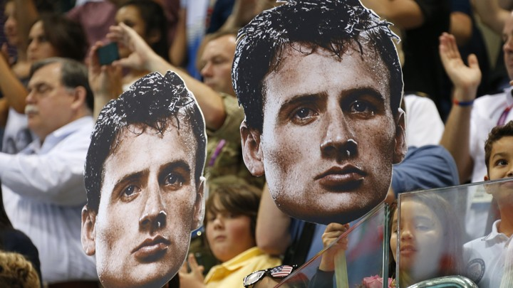 Fans at the 2012 London Olympics hold cutouts of U.S. Olympic swimmer Ryan Lochte.