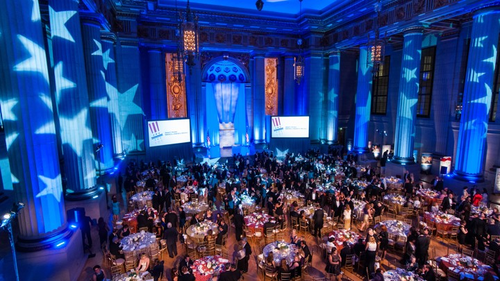 Large blue event hall filled with tables of guests