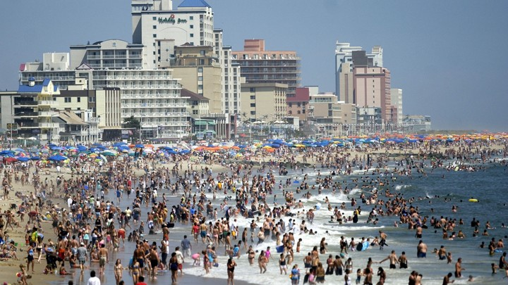 People and beach umbrellas pack the shores of Ocean City, Maryland. Hotels and other buildings also dot the coastline.