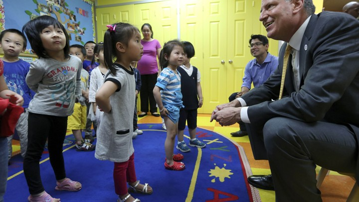 New York City Mayor Bill de Blasio smiles at children in a pre-k classroom in Brooklyn.