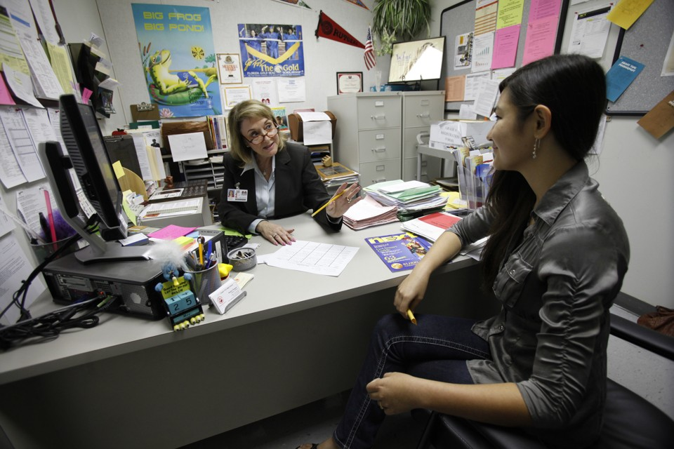 A high-school guidance counselor speaks to a student.
