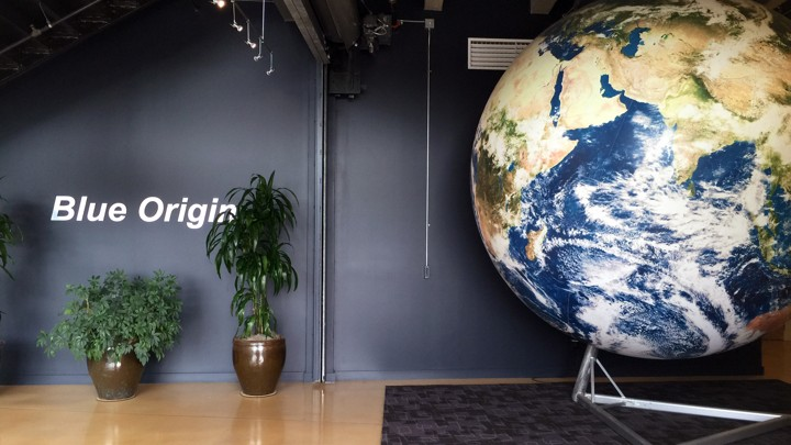 The Washington State office of the spaceflight company Blue Origin is shown, and include a replica of the Earth, some potted plants, and the company's name printed on the blue wall