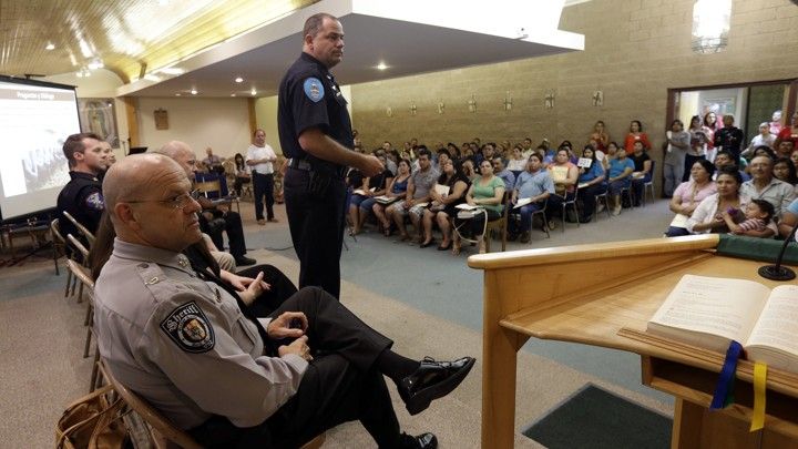 Police officers face rows of Latino residents in a meeting room.