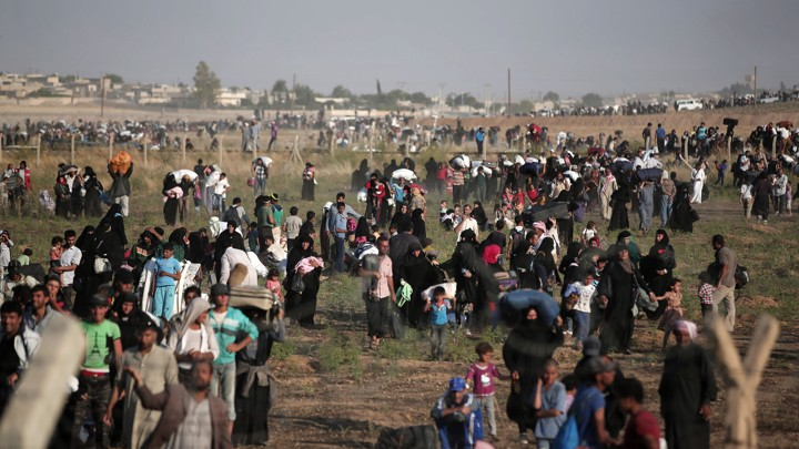 Thousands of Syrian refugees walk in order to cross into Turkey in June 2015.