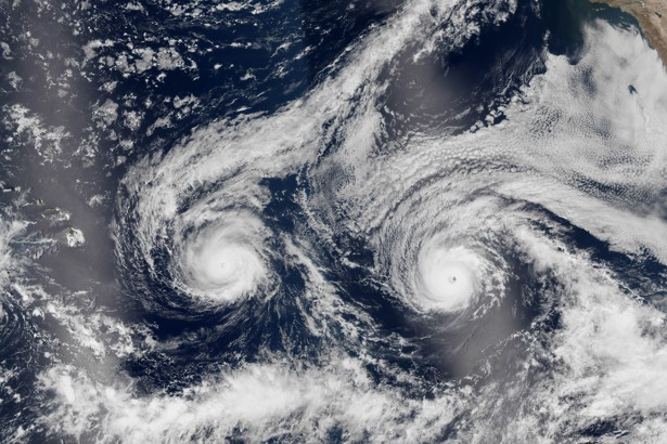 A tropical storm and a hurricane approach Hawaii as seen from satellite images.
