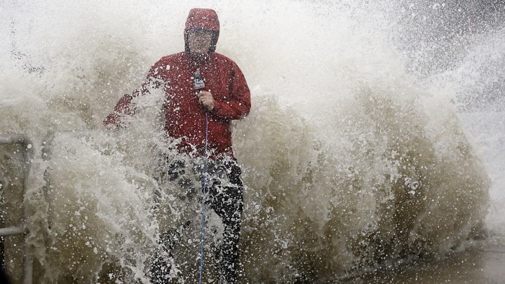 A news reporter doing a stand up near a sea wall in Cedar Key, Fla., is covered by an unexpected wave as Hurricane Hermine nears the Florida coast, Thursday, Sept. 1, 2016.