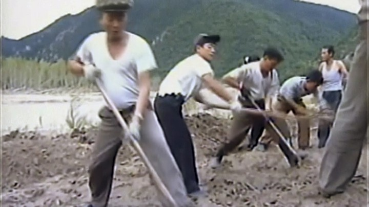 Workers build levees along a river bank in North Korea, where flooding has caused significant damage in the country's north-eastern province.