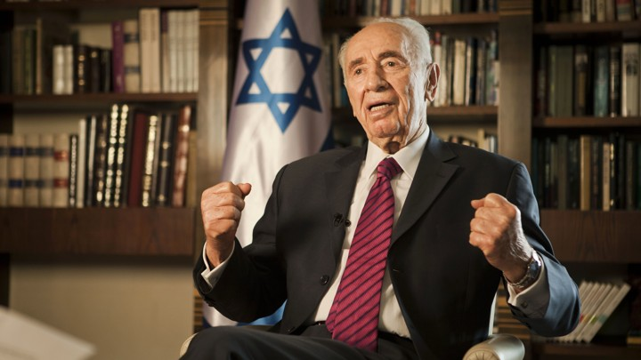 Shimon Peres gestures as he sits in front of bookshelves and an Israeli flag.