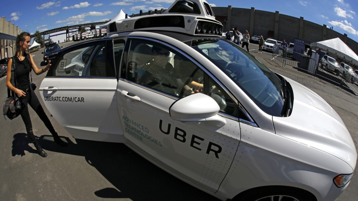 A journalist gets in a self driving Uber for a ride during a media preview at Uber's Advanced Technologies Center in Pittsburgh Monday, Sept. 12, 2016.
