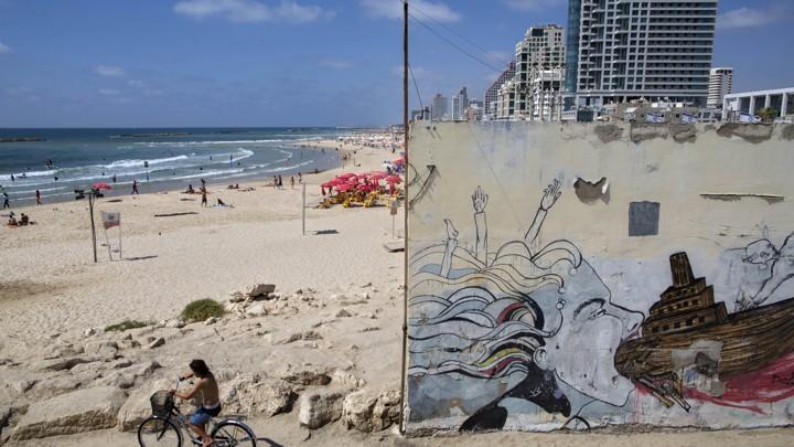 A boy rides a bike on Tel Aviv's beach front.