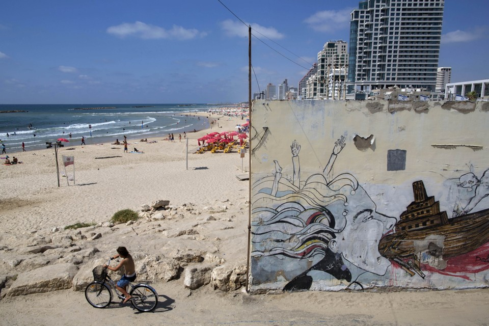 A boy rides a bike on Tel Aviv's beach front.