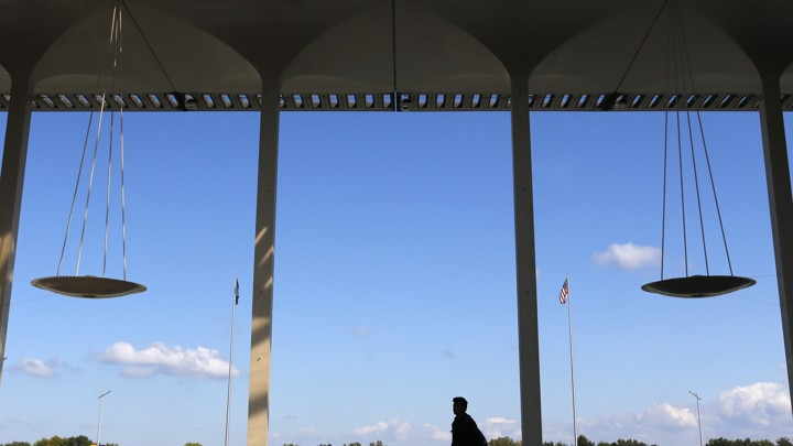 An image of the interior of a building where the silhouette of a person crosses midway through the frame; clear blue skies in the background; four columns visible in the image.