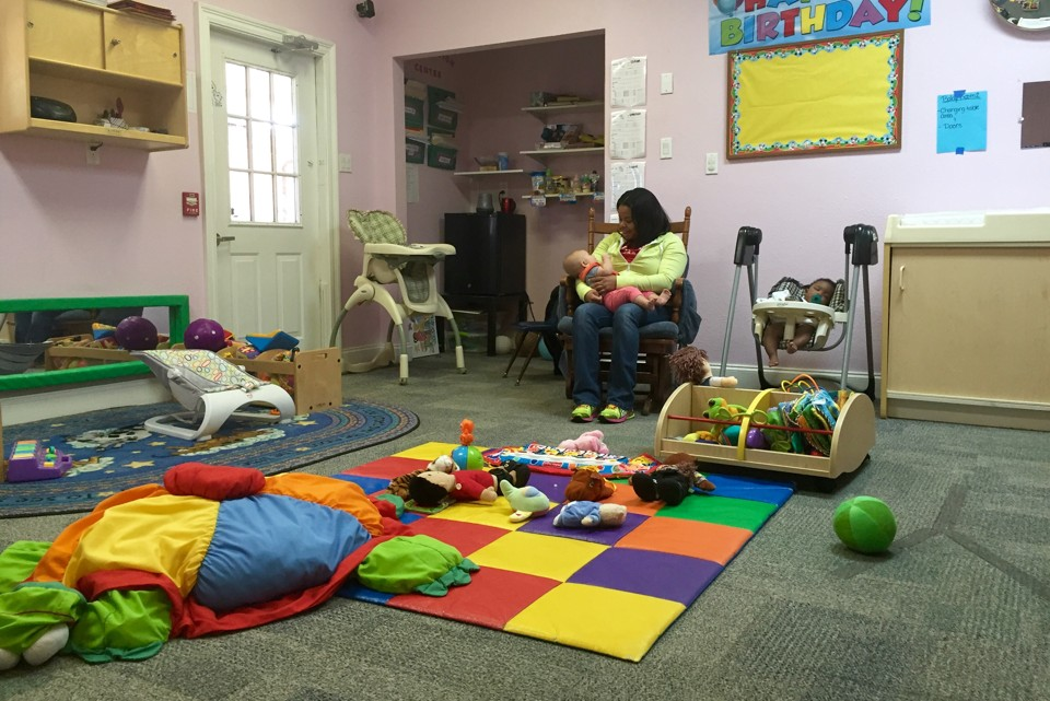 A woman holds a baby in a room filled with colorful toys and rugs.